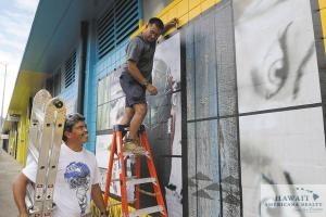 Eugene Price, left, owner of PD Technologies, and employee Darren DeMello install vinyl artwork on the side of a building in Kakaako.